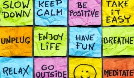"""Slow down. Keep Calm. Be positive. Take it easy. Unplug. Enjoy life. Have fun. Breathe. Relax. Go outside. Meditate."" Picture of a bunch of postit's with positive sayings on them and one with a smiley face."