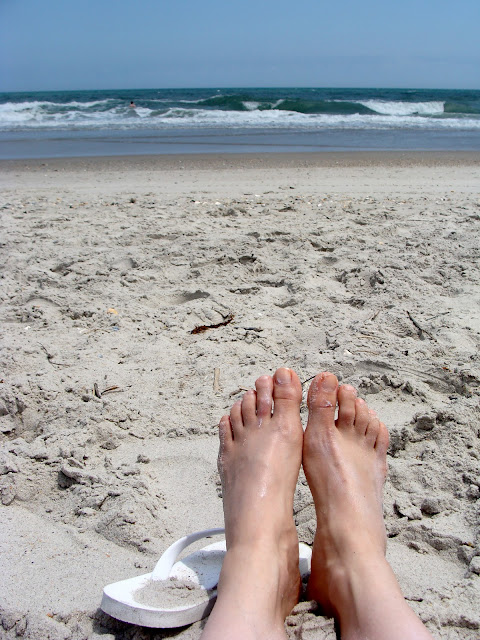 warm sandy beach with flip flops and toes in the sand