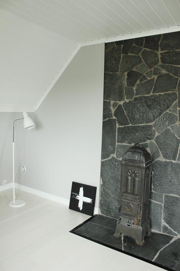 kamin gjutjärn på övervåningen, stenparti vid kamin, vitt plankgolv, vit parkett, grå matta väggar, vit lampa, tavla med kors, bilder på efter renovering, atlejé i grått och vitt