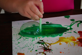 preschooler enjoying painting with a straw
