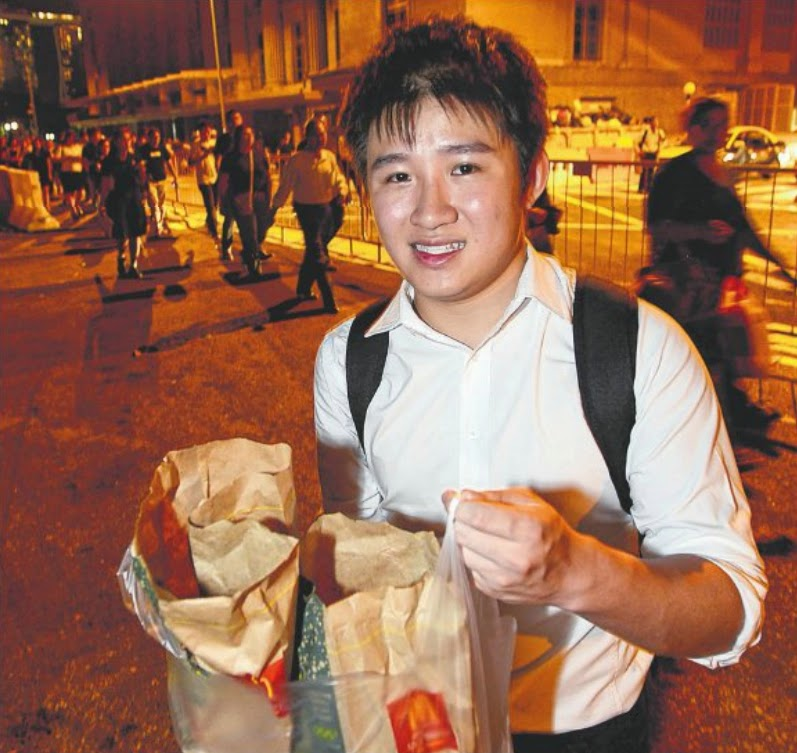 Act of kindness: Singapore Management University student Koh Kang Liang, 22, dug into his own pocket and bought 20 burgers for those waiting to enter Parliment House.