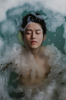 young asian man half submerged in bubble bath