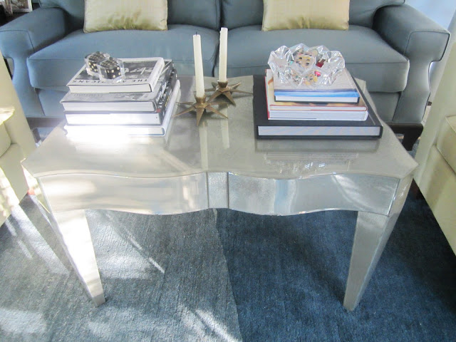 Close up of lucite coffee table with an eglomise finish and curved top, stacks of books and two candles in start shaped candleholders