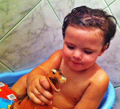 Miguel na banheira brincando com seu dinossauro