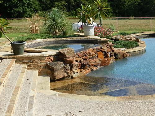 Home and garden artificial rocks around swimming pool for Gardens around swimming pools