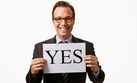 Guy smiling holding a piece of paper that says yes