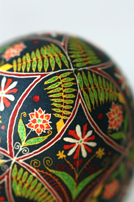Circular Geometric Floral and Fern Pysanky Ukrainian Egg in Scarlet, Green, Yellow on Black Background