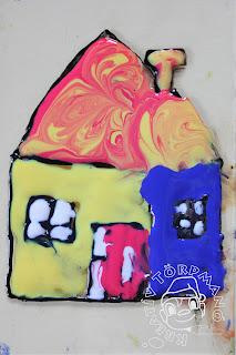 Szöveg: ... ez meg itt a házuk. :) Kép: A kifestett Törpmanó házikó ajtja fehér-piros csíkozású, egyik oldala kék, másik sárga, a háztető meg piros-sárga-narancssárga kombinációjú.