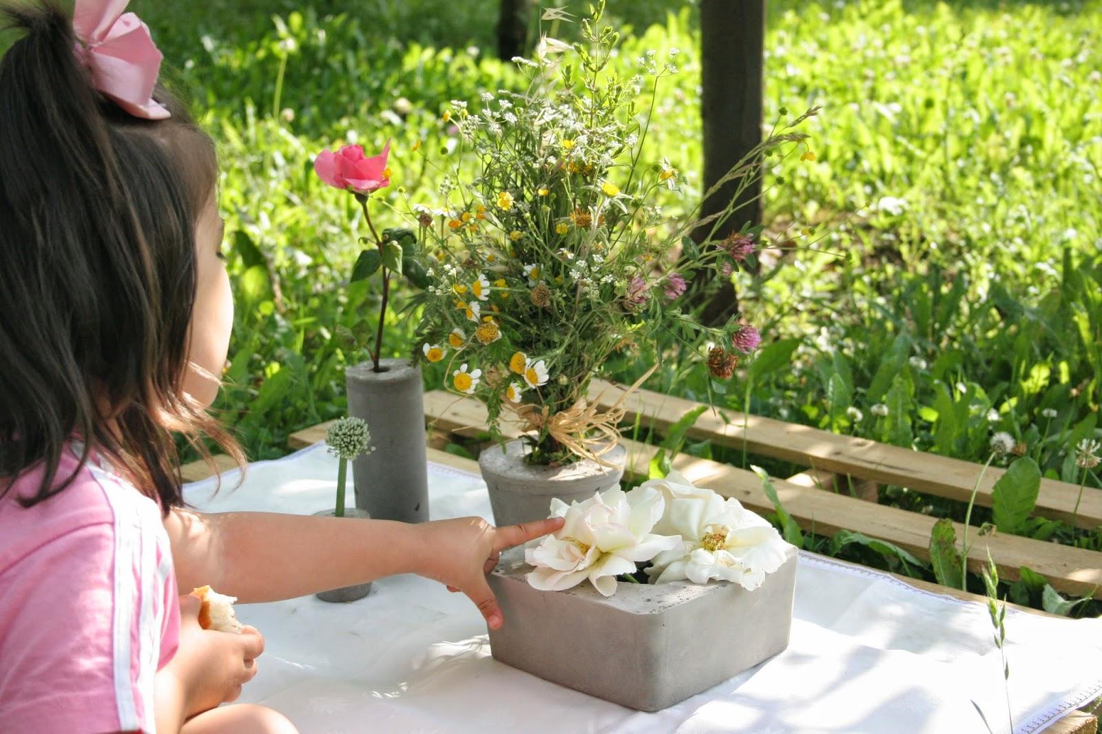 Mi niña decorando la mesa del picnic de la huerta con un palet y los diy floreros de cemento
