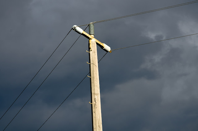 power pole with dark clouds behind