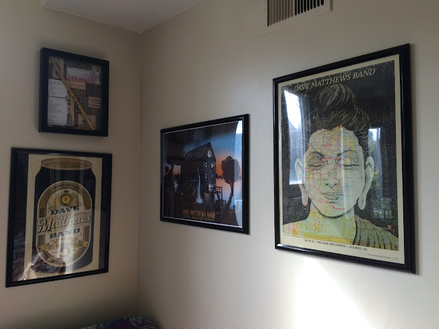 Photograph: The corner of an apartment. On the left wall are a picture box frame displaying a drumstick and a beer-themed DMB poster. On the right wall are a mill-themed DMB poster and a Buddha-themed DMB poster.