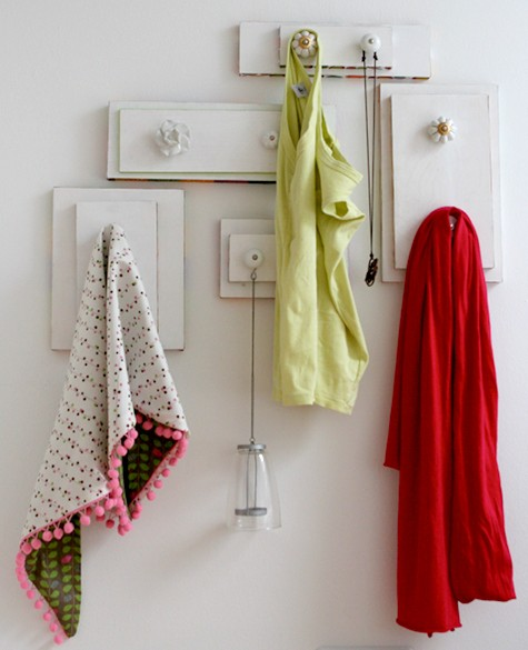 These drawer handles on the wall are a whimsical way to hang clothes and towels.