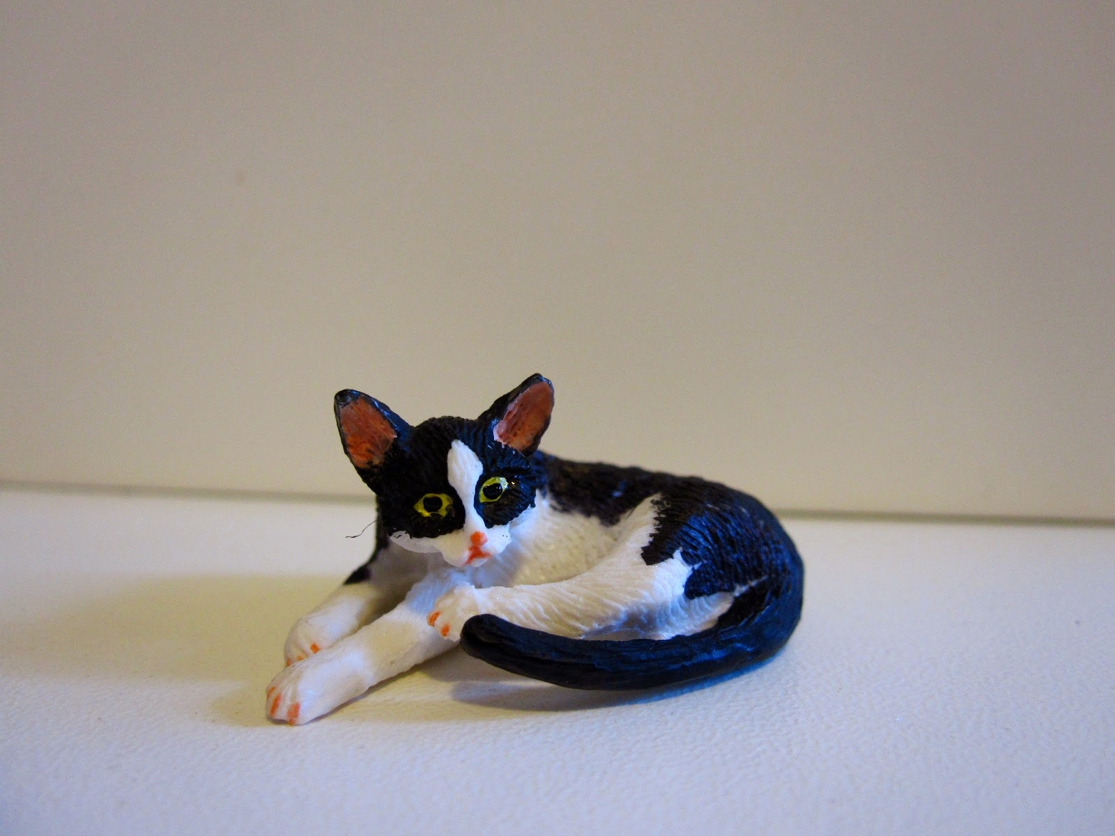 Dolls' house miniature black and white cat, lying down.