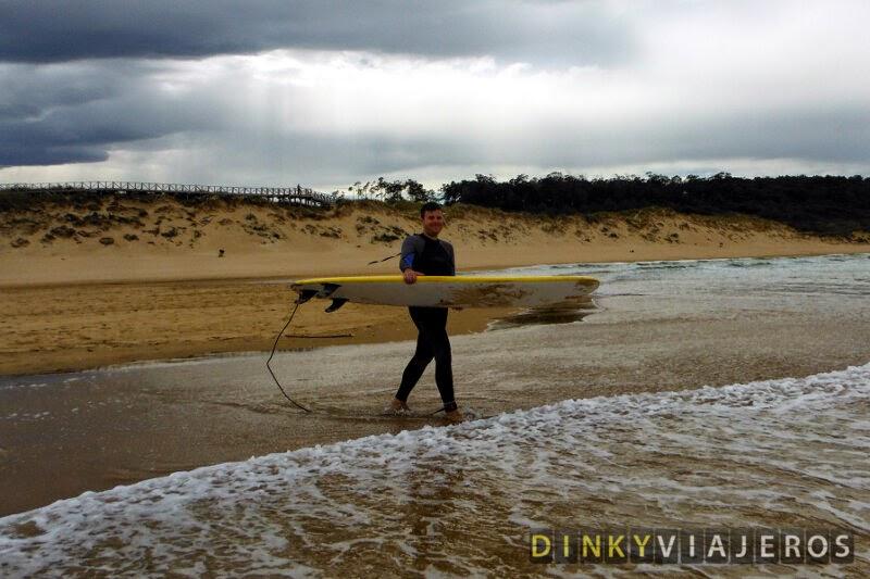 Clase de surf en Loredo (Cantabria). Víctor entra al agua con la tabla