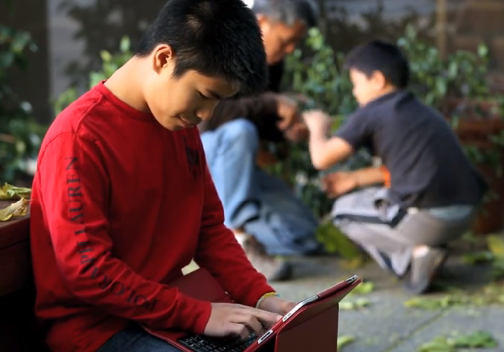 Photo of a boy seated outdoors, holding an iPad in his lap, looking at and touching the screen.