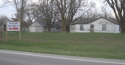 Run-down looking house and gray farm outbuildings with pristine handmade sign in front yard