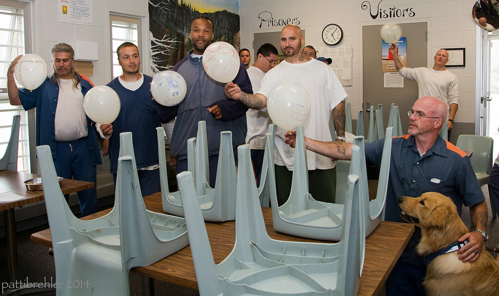 Six men are holding up white balloons with faces drawn on them. Four of the men are standing behind a table with four light blue plastic chairs upside down on the top of the table. The fifth man is behind the table too, but is sittin down. He has his left hand on the shoulder of a golden retriever who is sitting in front of him. In the background behind this man is another man holding a ballon up high.There are a few more men behind the group, not very muc in view. The are in a room with white brick walls.