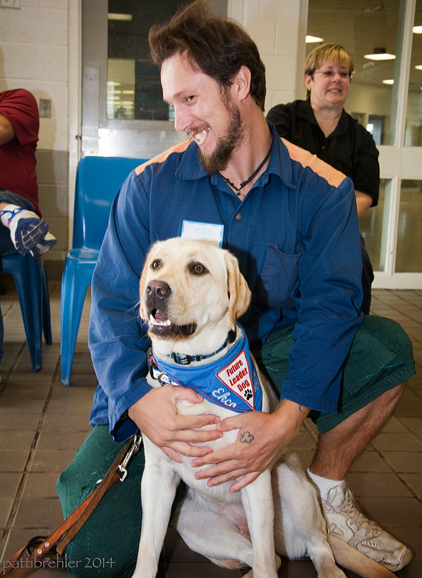 A man wearing the blue prison shirt with green pants is squatting on a tile floor with a young yellow lab sitting between his legs. The man's hands are wrapped around the dog's chest. The dog is wearing the blue Future Leader Dog bandana and is looking toward the camera, with his leash hanging to the left. The man has his head turned to the left and is smiling devilishly at the camera. There is a woman in the background over his left shoulder, she is wearing a black shirt .