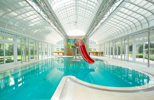 Mansion with indoor pool and a red water slide