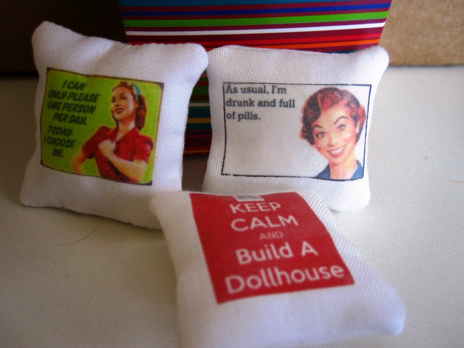 Three modern miniature cushions with funny slogans on them