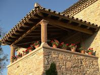 Detall del porxo amb teulada de triple vessant i amb una estructura de fusta sustentada per pilars de pedra amb capitells