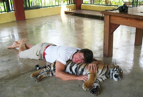 man and a baby tiger