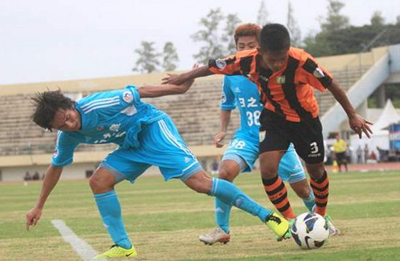 A Persibo Bojonegoro player fights for the ball with two Sun Hei players