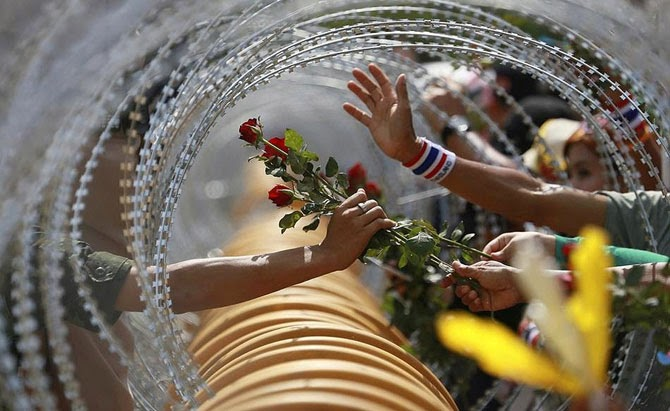 Антиправительственный демонстрант протягивает розу солдату во время протестов в Бангкоке, Таиланд, 2013.