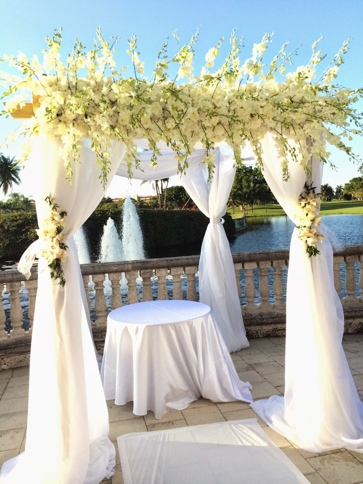 Luxurious and romantic white gazebo decorated with roses and orchids