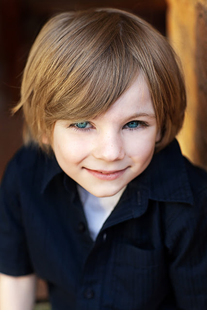 Male child with beautiful blue eyes staring at photographer's camera for portrait