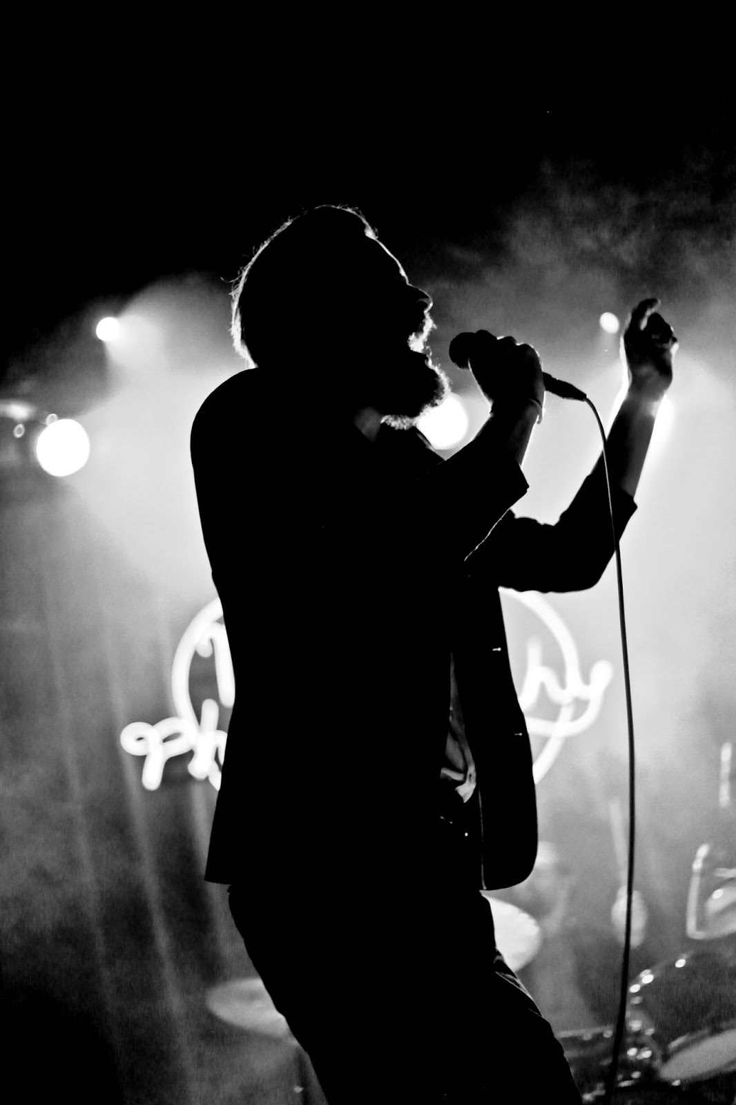 The silhouette of Joshua Tillman on stage at the Ogden Theatre.