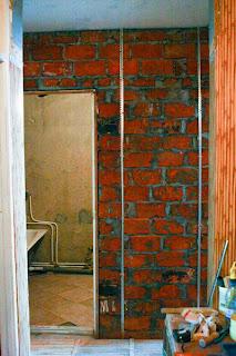 наружная стена ванной с установленными маячками для выравнивания