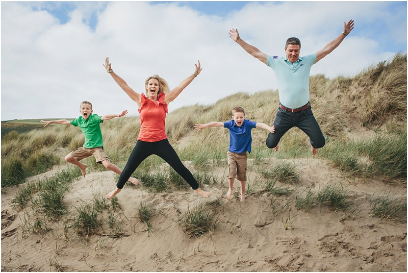 A family jumping off the sand dunes at Saunton Sands