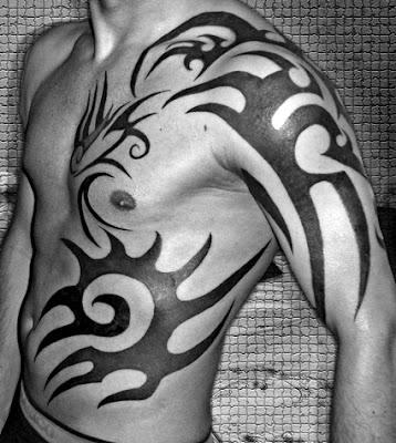 Tatuaje de tribales en brazo, pecho y abdomen