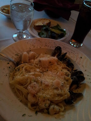 pasta, fettucini, fettucine, seafood, shrimps, mussels, scallops, white plate, glass of water, white tablecloth