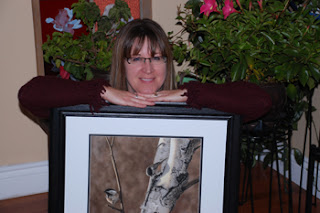 Colette Theriault and her pastel painting of black capped chickadee in a birch tree