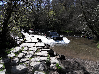 car driving through the river by Tarr Steps