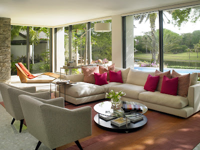 sandy hues clues this lounge area a coastal themed living room with glass walls for a gorgeous view outside