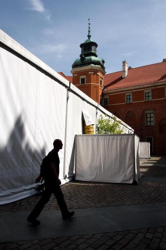 Fofo do largo interior do castelo com uma tenda branca gigante e um homem a passar em contra-luz