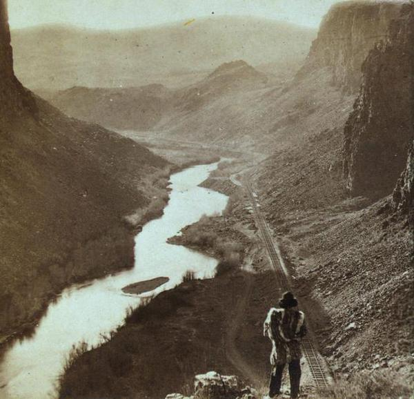 25 Breathtaking Photos From The Past - A Native American looks down at a newly-completed section of the transcontinental railroad. Nevada, about 1868