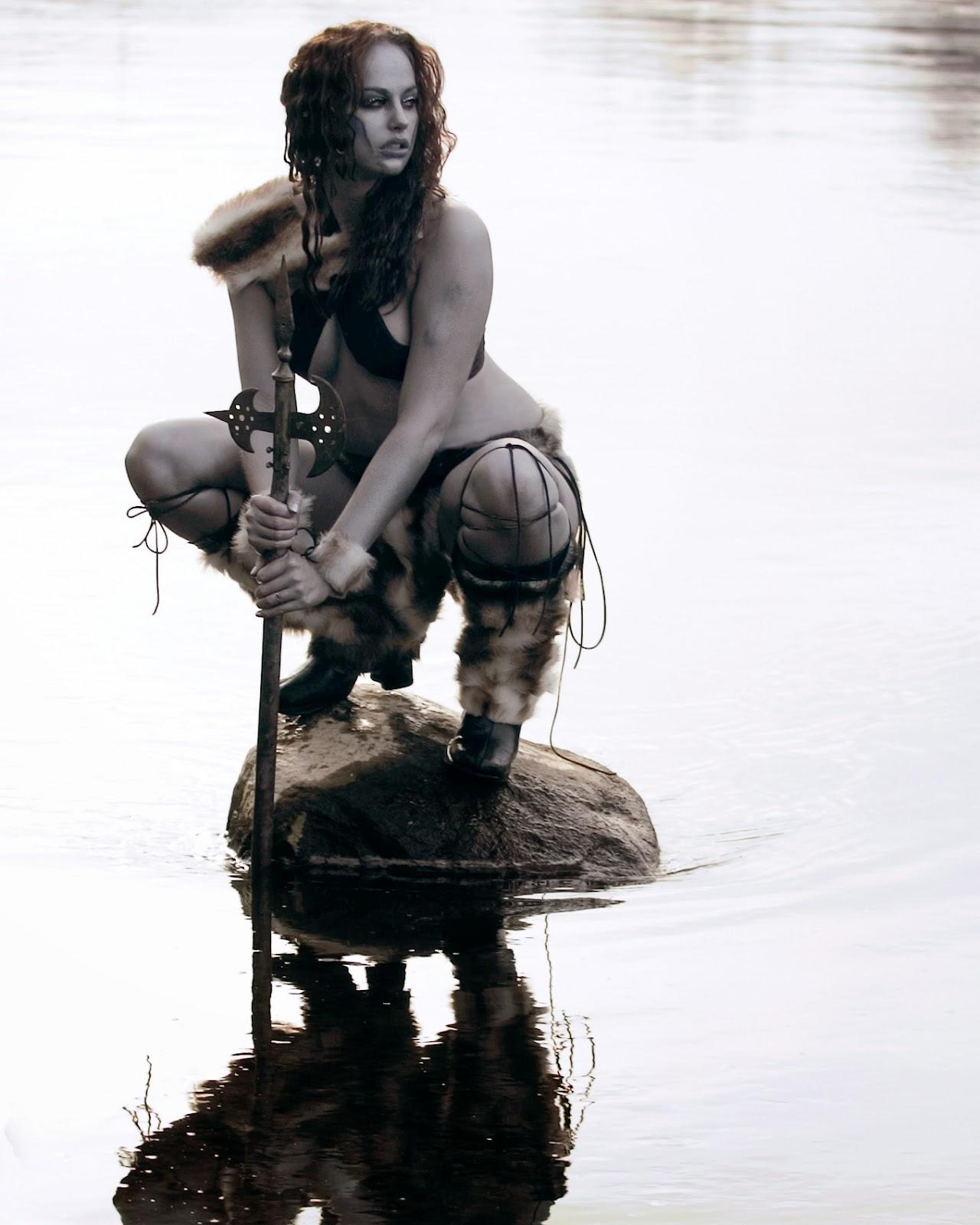 guerriere peau argentée accroupie sur un rocher au milieu d'une rivière