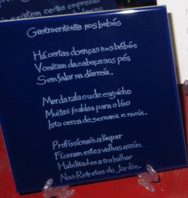 Pormenor da Velha Gastroenterite nos Bebés em Fotografia de Velhas da Ilha Terceira gravadas em azulejos em cima de mesa feita de barril de vinho