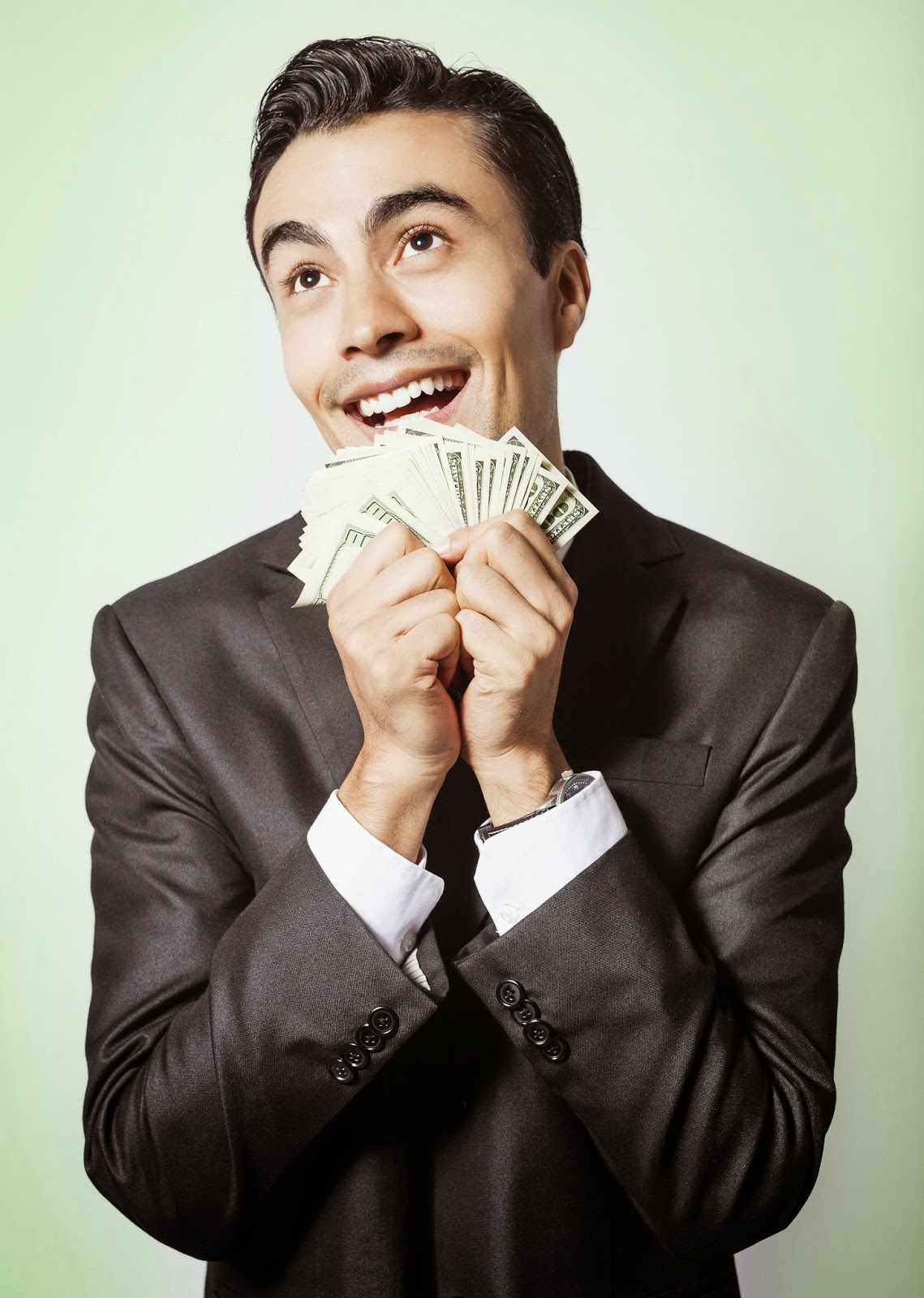 man in business suit holding fanned-out cash