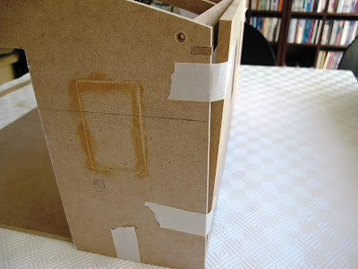 Close up of a corner of a half-built dolls' house shed, showing walls not meeting up properly.