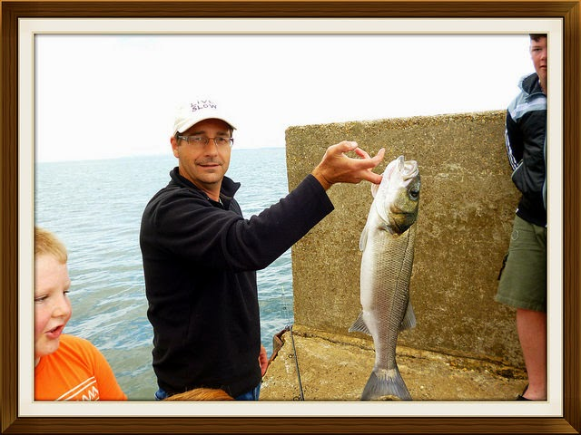 fisherman with large sea bass catch of the day