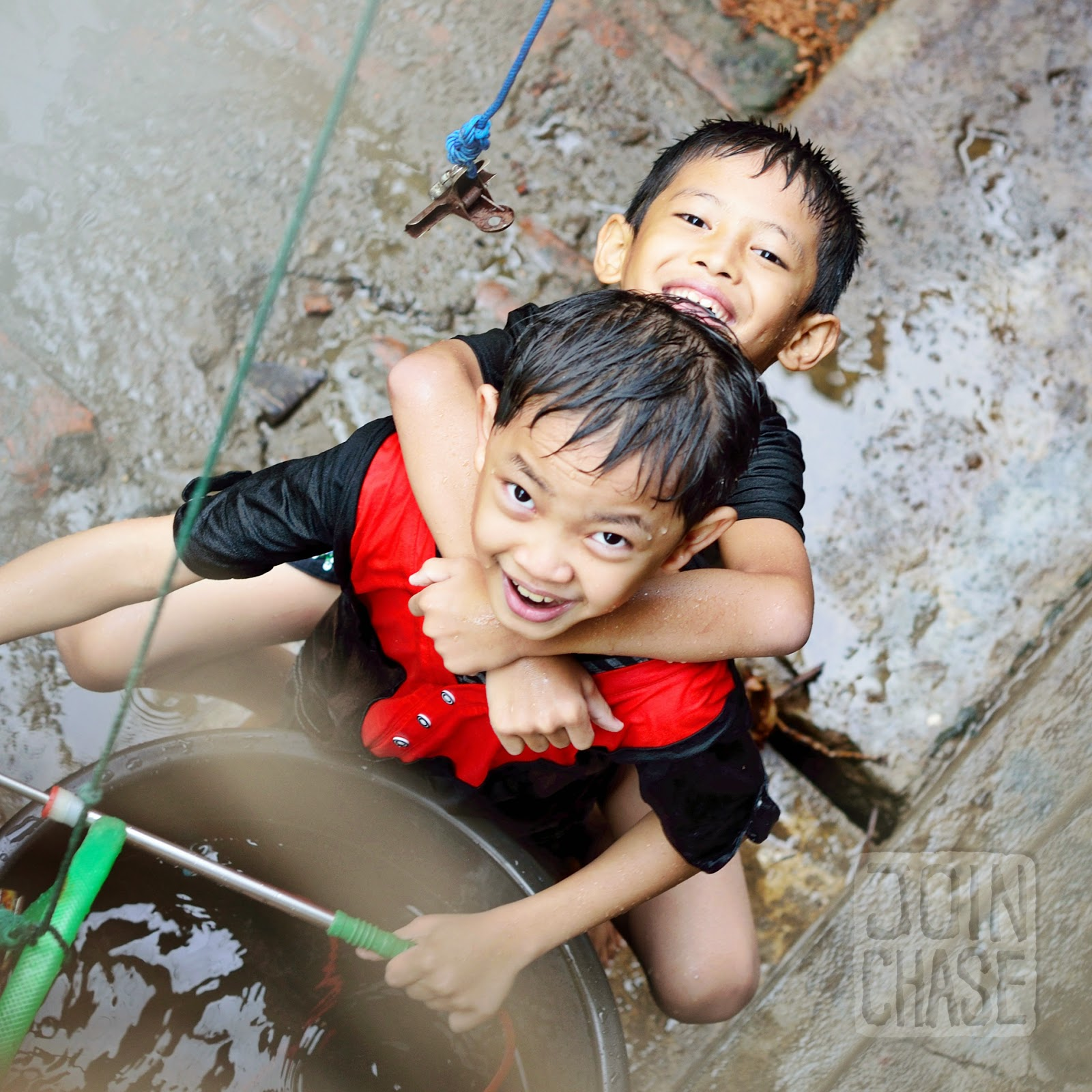 Two boys playing with water during Thingyan in Yangon, Myanmar.