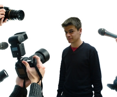 IMAGEM: Editor Rafael sendo fotografado em coletiva - Ficção
