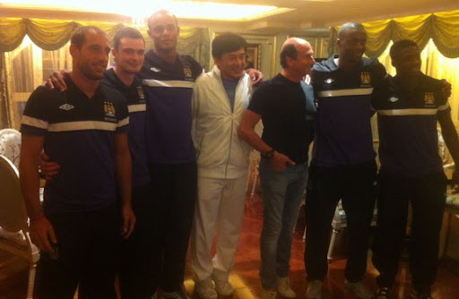 Hollywood star Jackie Chan takes a picture with Manchester City players