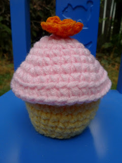 yellow cupcake with pink icing and orange flower crochet