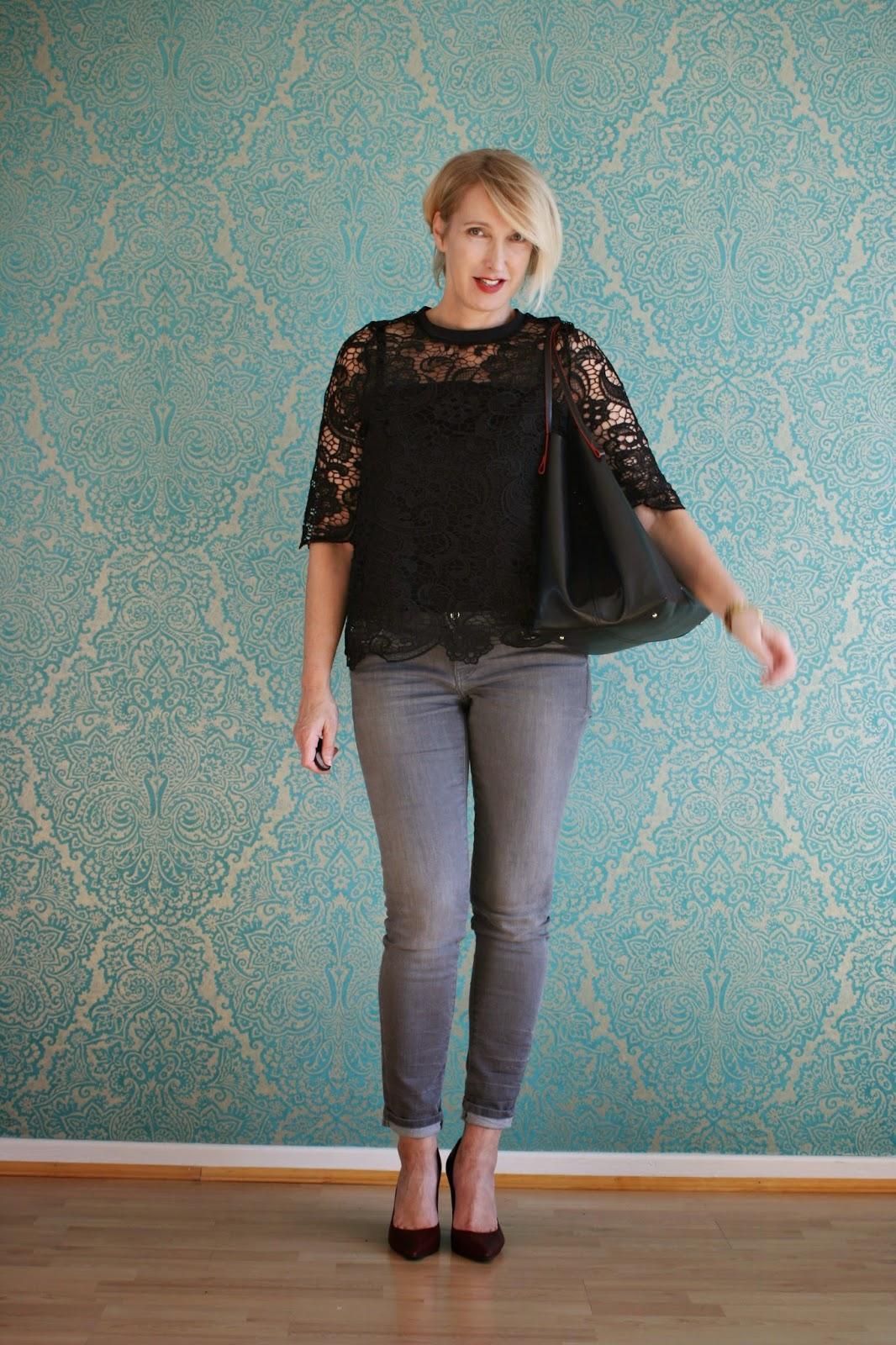 Schwarzes Spitzentop mit Jeans kombiniert